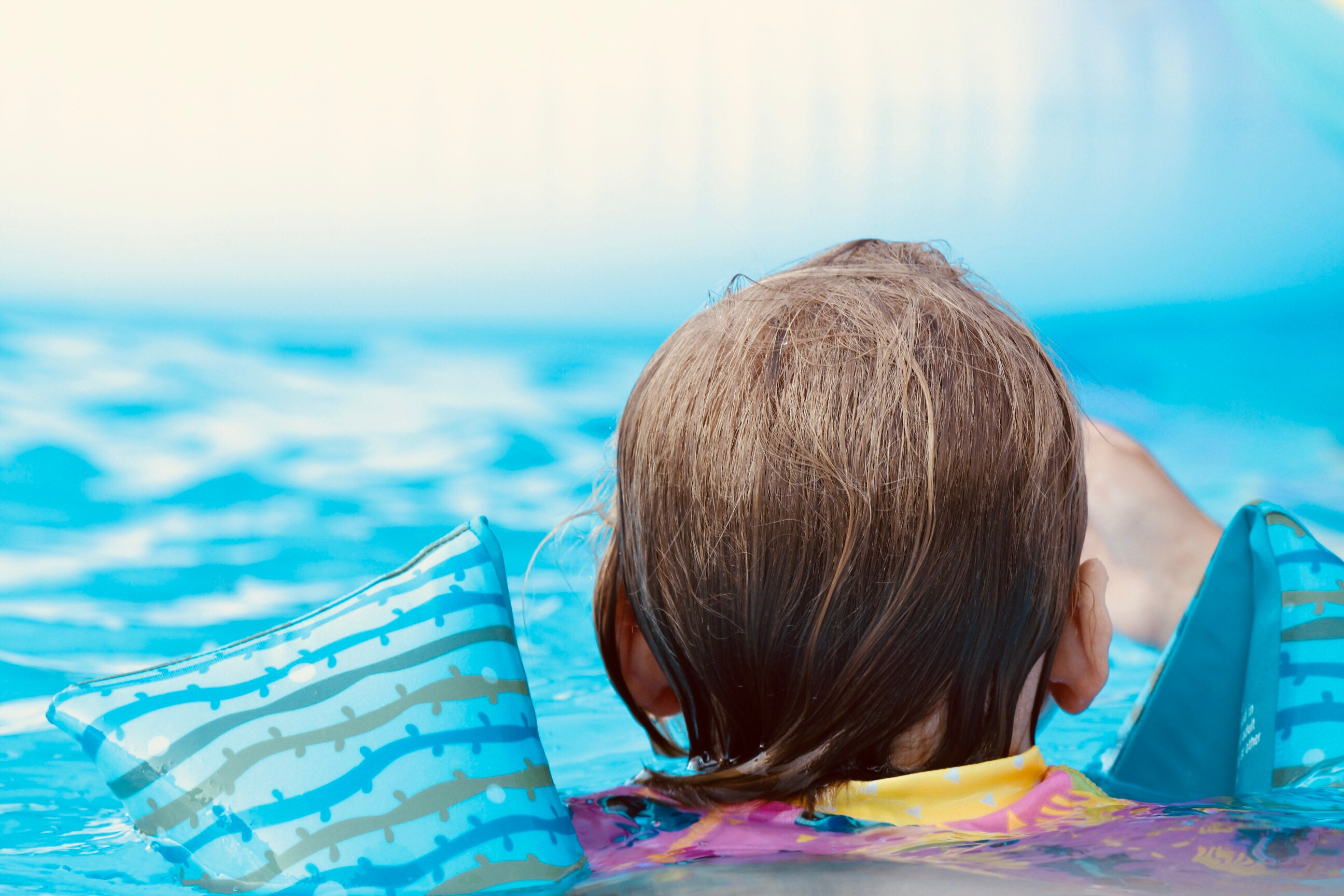child in pool with floaties
