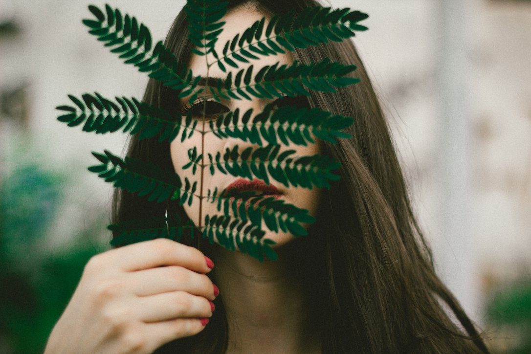 Woman hiding face behind a leaf